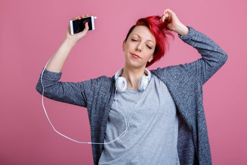 Une fille avec un aspect créatif, a plaisir à écouter la musique sur des écouteurs par le téléphone et la danse images libres de droits