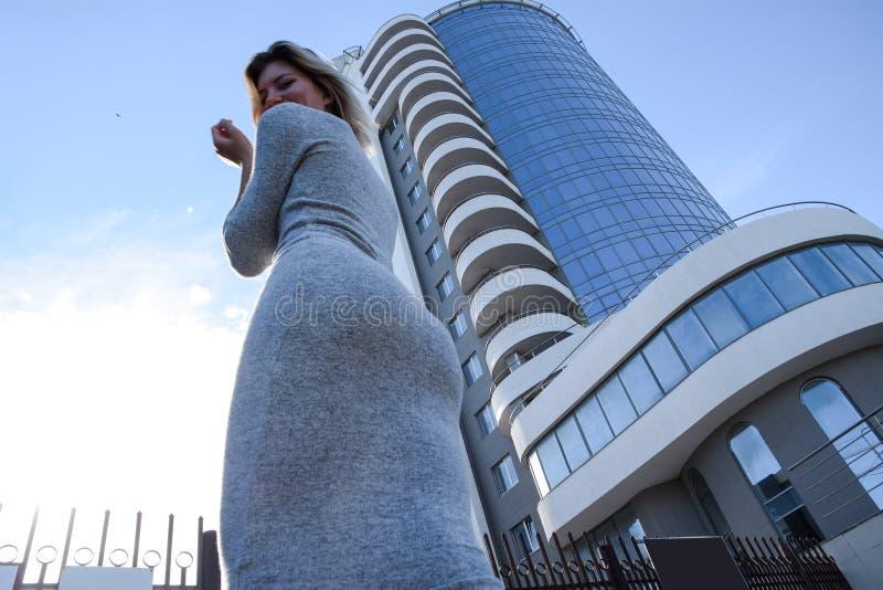 Une fille avec un beau chiffre dans une robe grise près d'un édifice haut photo libre de droits