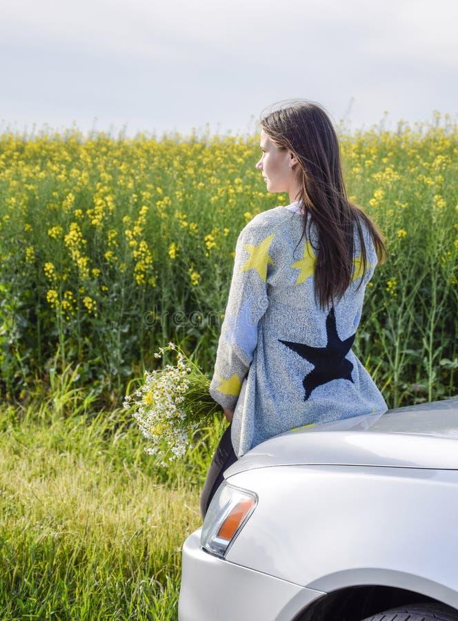 Une fille avec un bouquet des marguerites s'assied sur le capot de la voiture et examine la distance photographie stock libre de droits