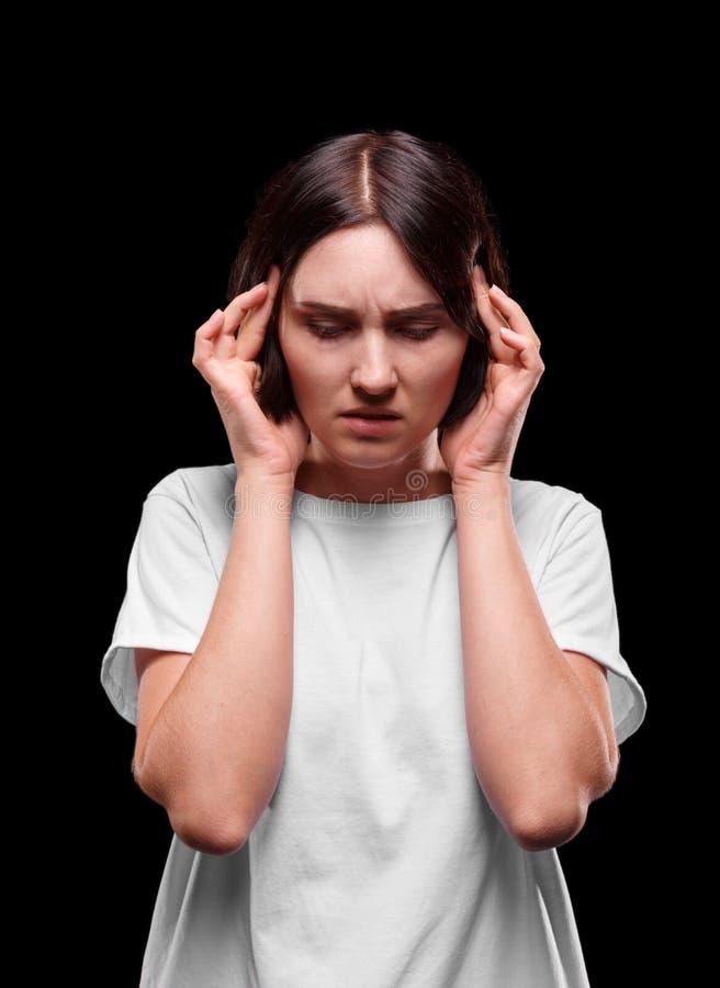 Une fille avec un mal de tête grave sur un fond noir Une jeune femme triste dans un T-shirt blanc massant ses temples images stock