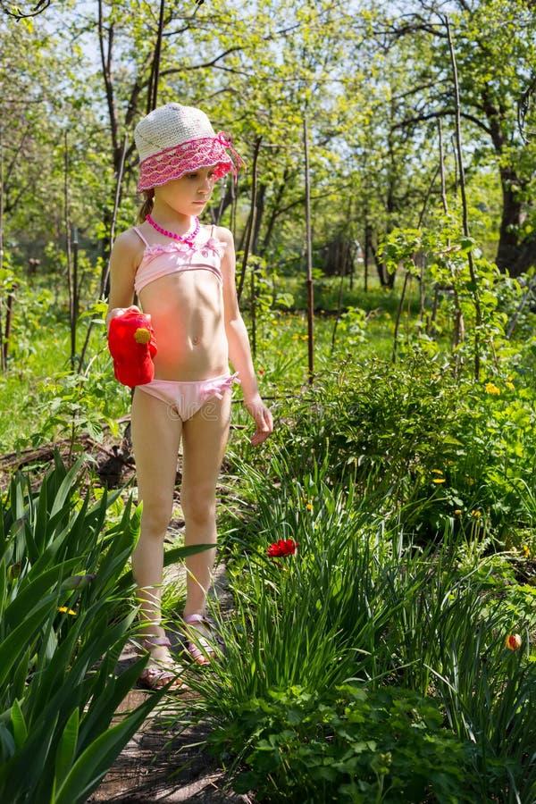 Une fille avec un pot d'arrosage photo libre de droits