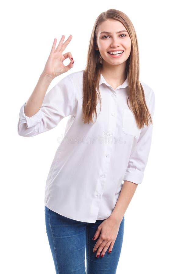 Une fille avec un sourire prouve que tout va bien sur un fond d'isolement par blanc images stock