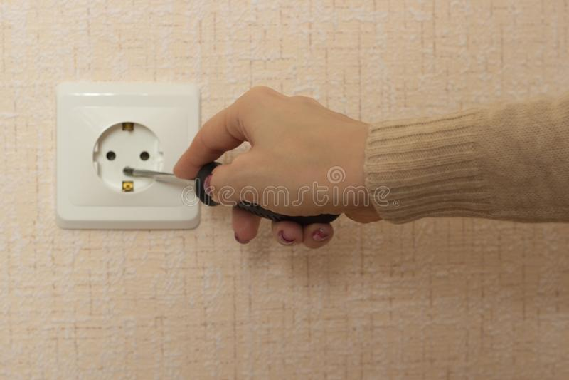 Une fille avec un tournevis répare un débouché électrique photographie stock