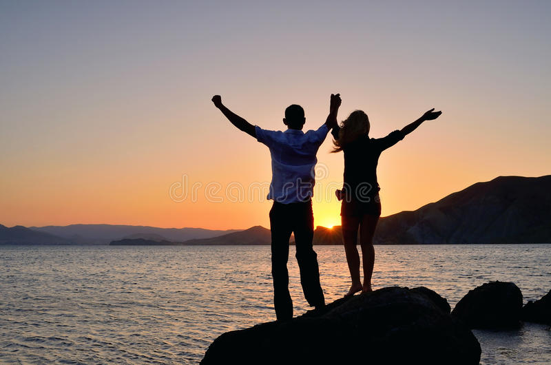 Une fille avec un type a soulevé ses mains au soleil image stock