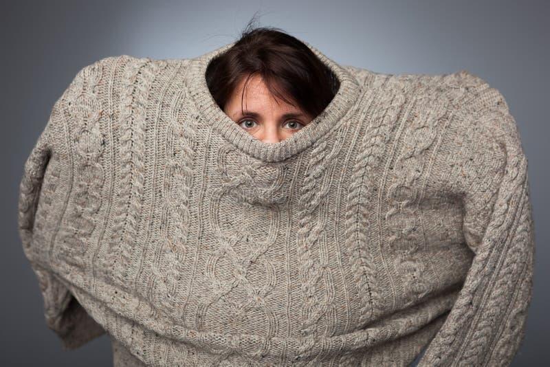Une fille avec une phobie sociale cache son visage dans un chandail photographie stock libre de droits