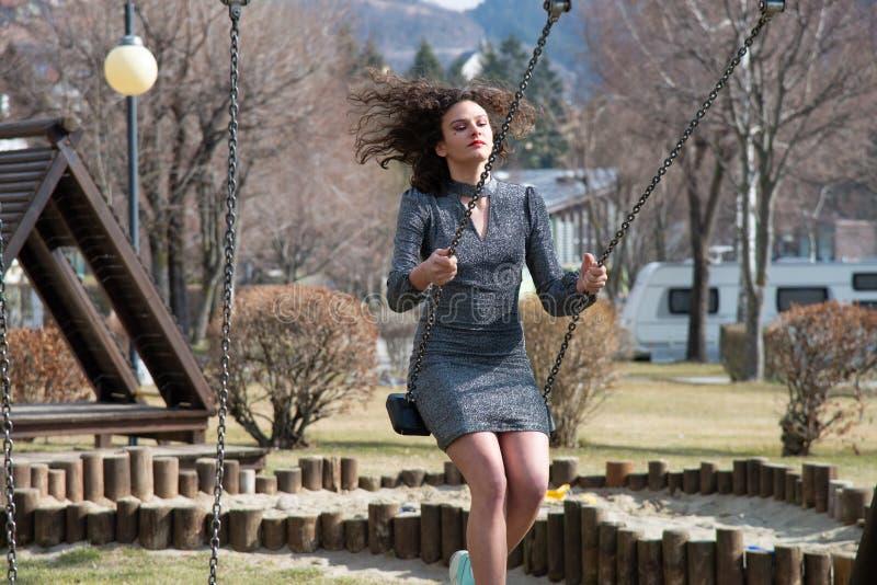 Une fille balançant sur une oscillation en bois d'un terrain de jeu, très heureuse photographie stock