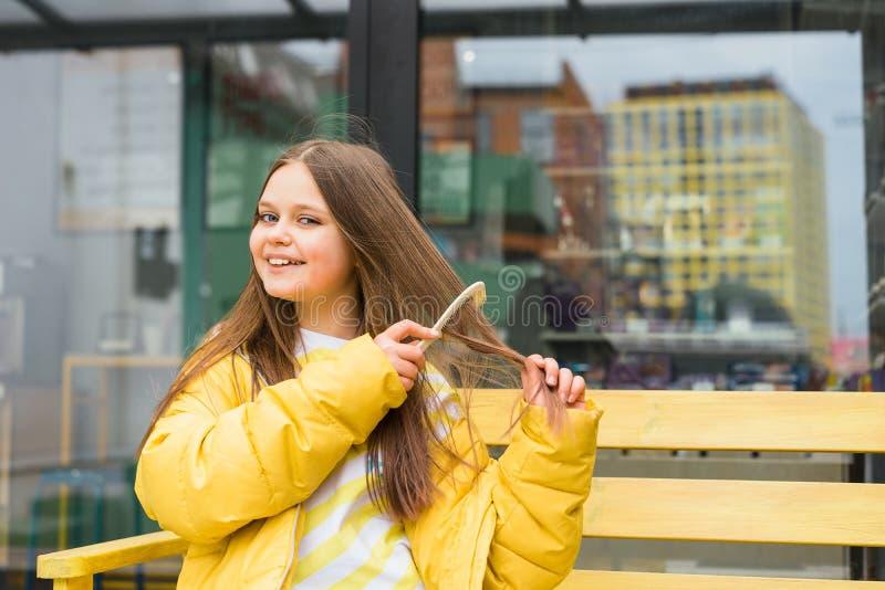 Une fille blonde aux cheveux longs et gaie se peigne les cheveux photographie stock