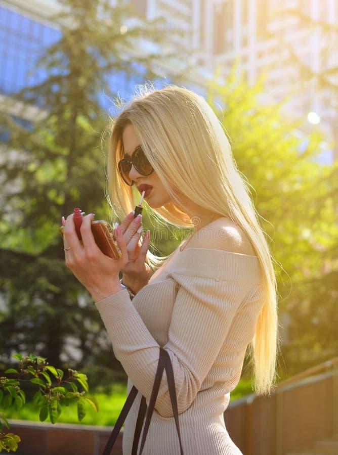 Une fille blonde chic dans des lunettes de soleil peint ses lèvres avec le rouge à lèvres rouge sur les gratte-ciel image libre de droits