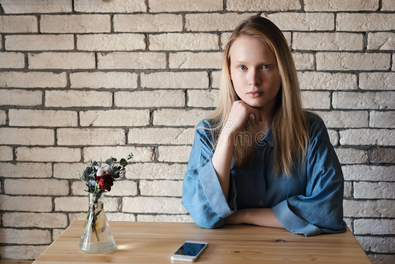 Une fille blonde dans la chemise bleue s'assied à la table dans un café et un regard photographie stock libre de droits