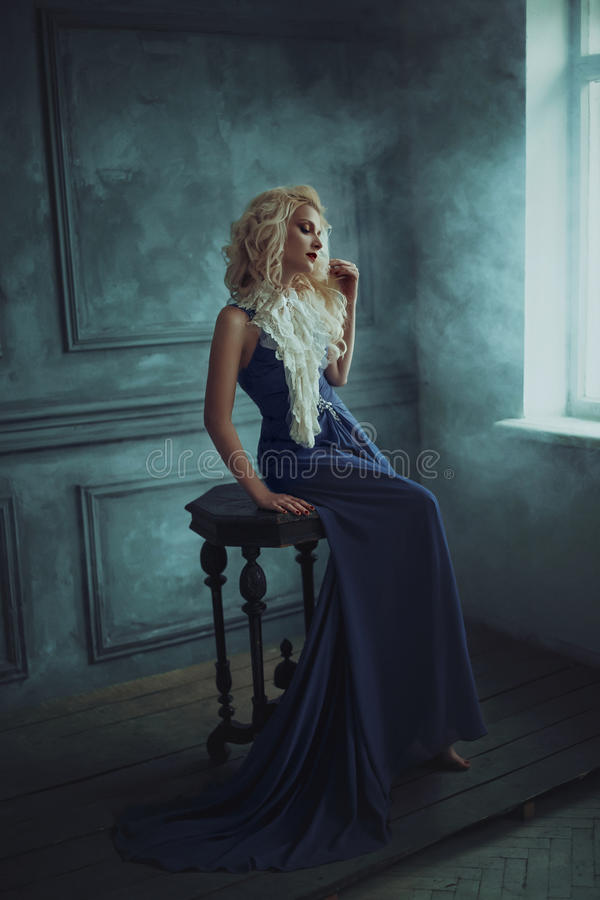 Une fille blonde dans une robe bleue luxueuse image stock