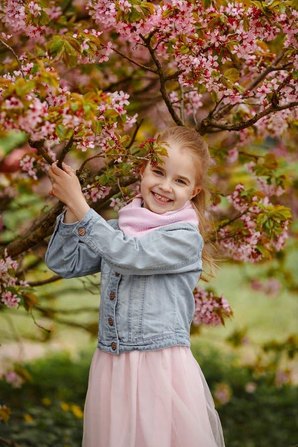 Une fille blonde mignonne sourit sur un fond des Bu roses de Sakura photos libres de droits