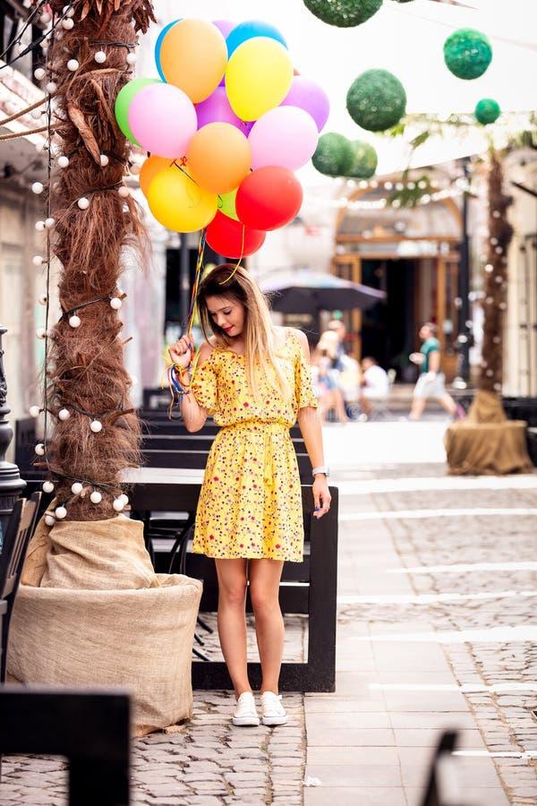 Une fille blonde sourit avec des ballons ? disposition photographie stock