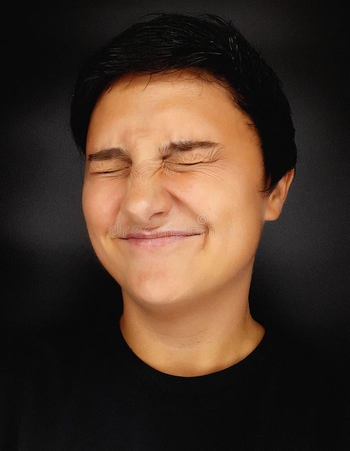 Une fille brunette aux cheveux courts sur fond noir dépeint diverses émotions humaines photos stock