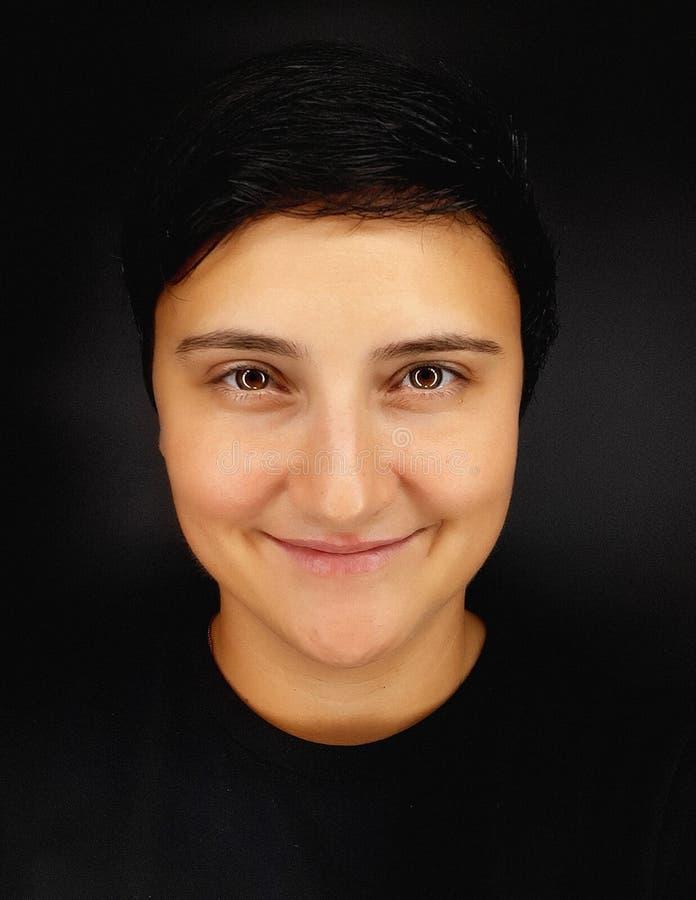 Une fille brunette aux cheveux courts sur fond noir dépeint diverses émotions humaines image stock