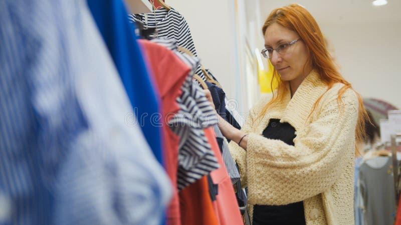 Une fille choisit une robe rayée dans un magasin d'habillement du ` s de femmes image stock