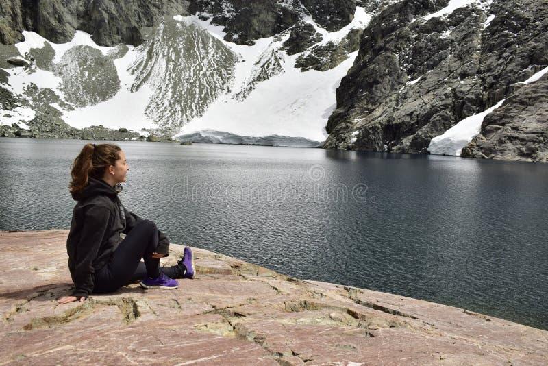 Une fille contemple les montagnes et les glaciers qui tombent à un lac photos libres de droits