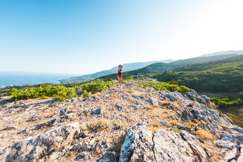 Une fille court dans les montagnes Une femme va chercher dedans des sports en nature images stock