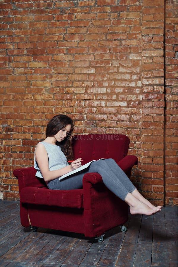 Une fille d'adolescent écrit dans un carnet de journal intime se reposant dans une vieille chaise sur une station abandonnée somb photo stock