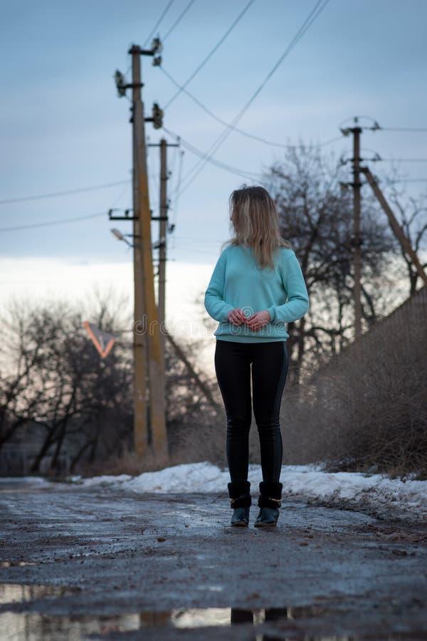 Une fille dans des guêtres noires et un chandail bleu se tient sur le fond des lignes de la transmission et regarde loin image stock