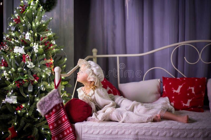 Une fille dans des pyjamas se trouve sur un lit à côté d'un arbre de Noël images stock