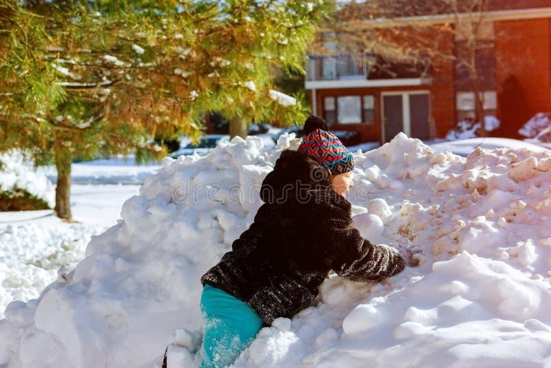 Une fille dans des vêtements d'hiver court à une colline de neige avec jouer en hiver avec la neige photo stock