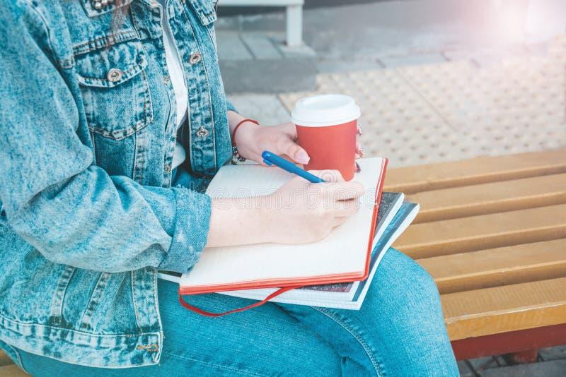 Une fille dans des vêtements de jeans s'assied sur un banc, tient des carnets et écrit Sur la rue, elle écrit dans un carnet, étu image stock