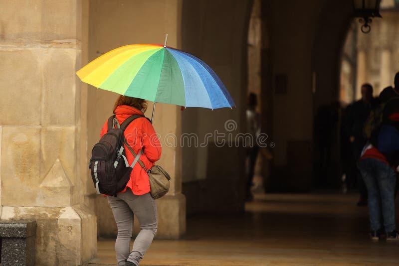 Une fille dans des vêtements lumineux d'automne avec un grand parapluie de toutes les couleurs des promenades d'arc-en-ciel dans  photo libre de droits