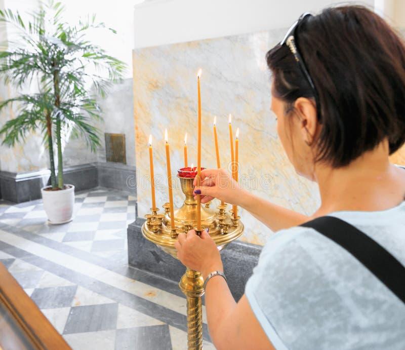 Une fille dans l'église place une bougie brûlante dans un chandelier image stock
