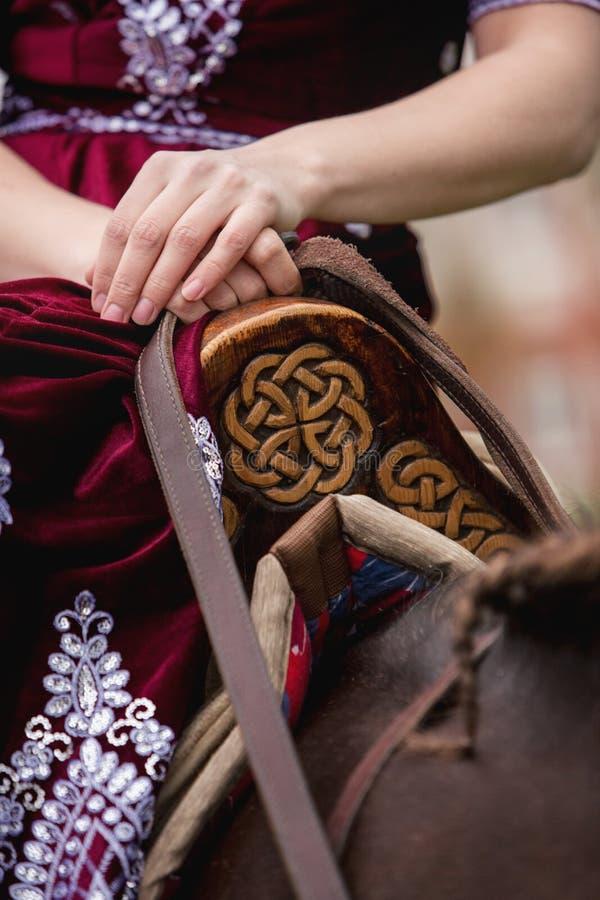 Une fille dans la robe classique tapote son cheval sur le fond du château photo libre de droits