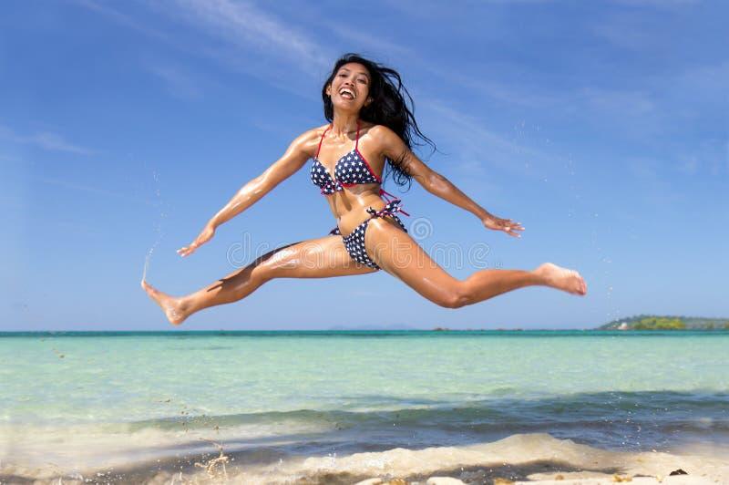 Une fille dans le bikini sautant sur la plage de mer image libre de droits