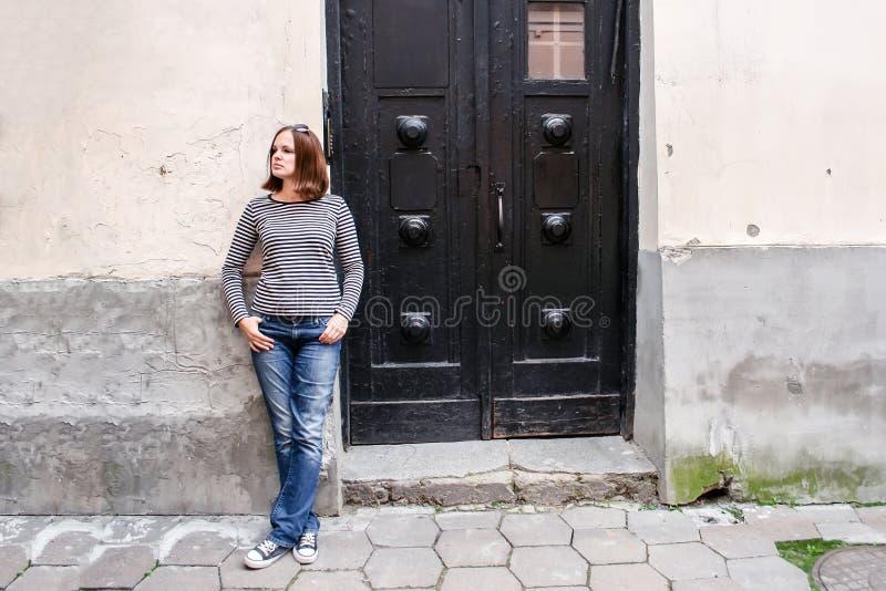 Une fille dans les jeans, un chandail rayé et des espadrilles se tient près de la porte en bois noire d'une vieille maison et des photos libres de droits