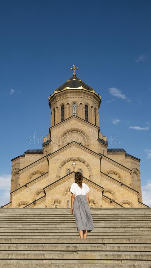 Une fille dans une longue robe se tient sur le fond d'un vieux temple chr?tien photos stock