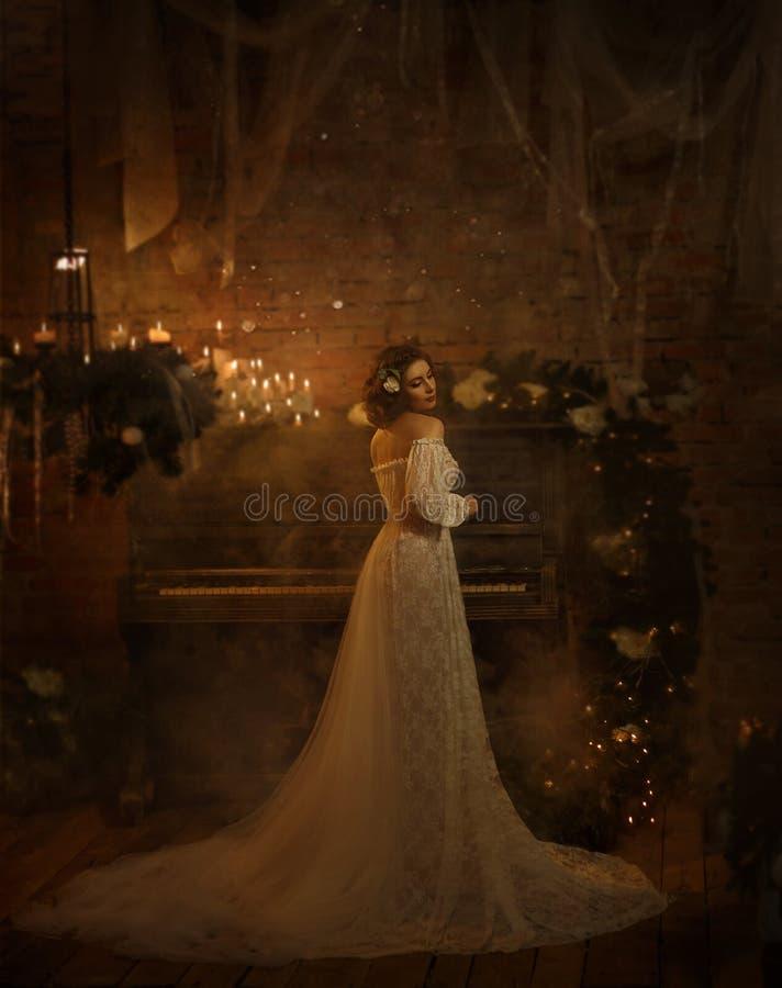 Une fille dans une robe blanche de vintage avec les épaules ouvertes se tient dans la perspective d'un vieux piano et des bougies photographie stock libre de droits