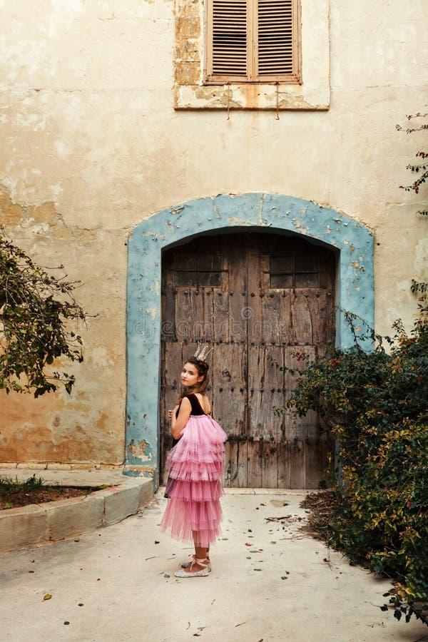 une fille dans une robe féerique d'une princesse avec une couronne tourne autour le walkng à la porte d'une maison antique de châ photos stock