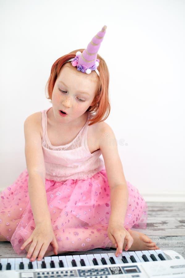 Une fille dans une robe intelligente joue le piano et le chant photos stock