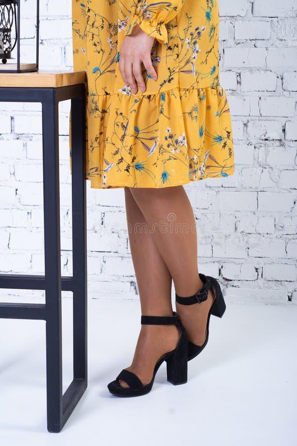 Une fille dans une robe jaune lumineuse près du tabouret de bar : seulement les jambes et le fond de la robe sont évidents photos libres de droits
