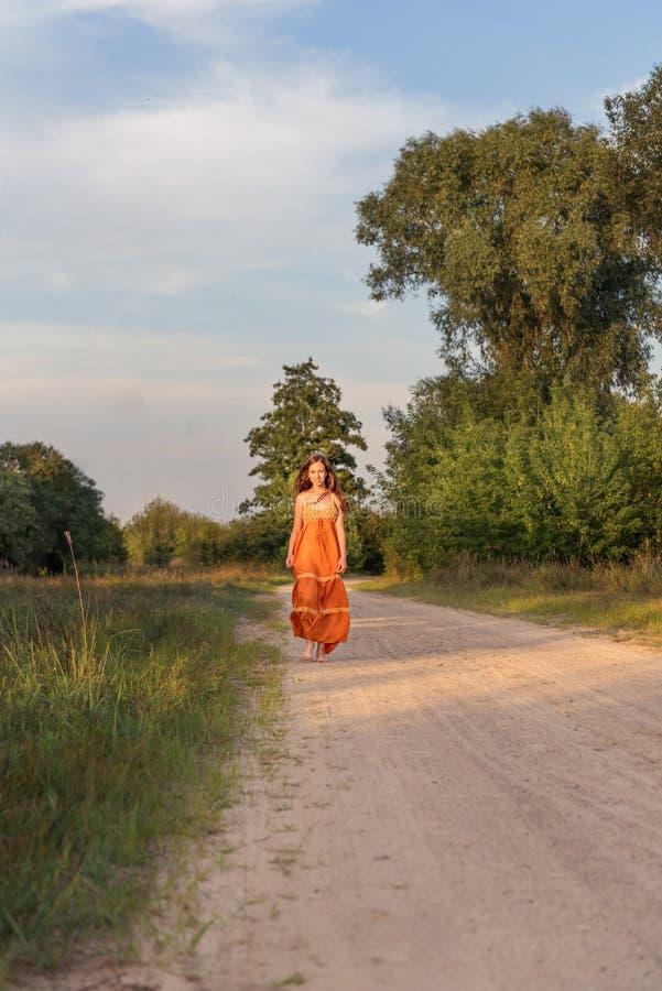 Une fille dans une robe long d'été rural marche nu-pieds le long d'une route arénacée de pays au coucher du soleil dans le villag photo libre de droits