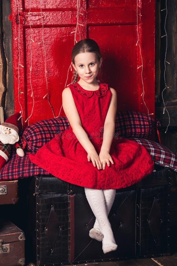 Une fille dans une robe rouge s'assied sur de vieilles valises image libre de droits