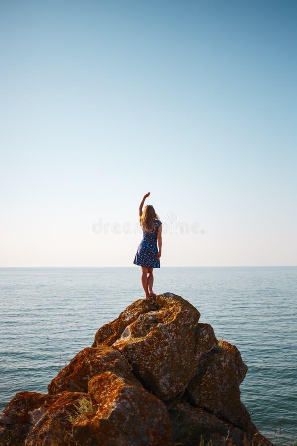 Une fille dans une robe se tient sur une pierre et des regards à la mer bleue photographie stock libre de droits