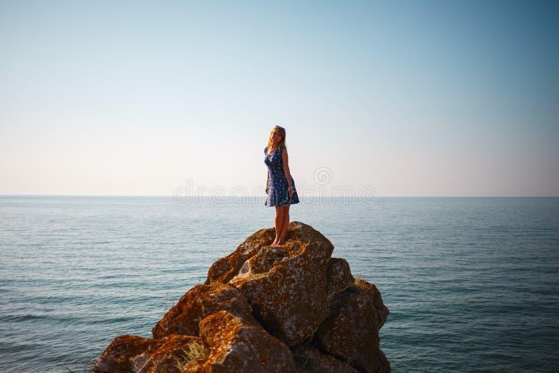 Une fille dans une robe se tient sur une pierre et des regards à la mer bleue image libre de droits