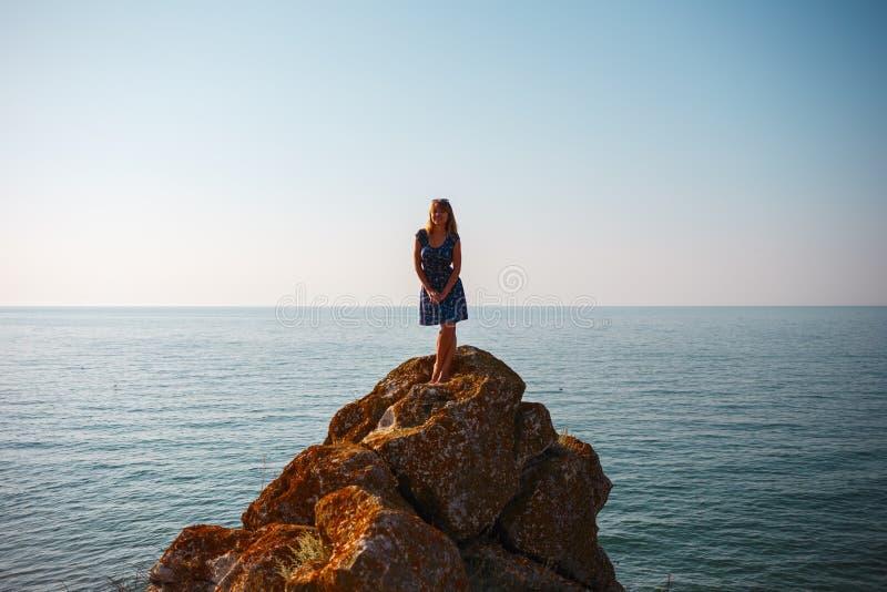 Une fille dans une robe se tient sur une pierre et des regards à la mer bleue image stock