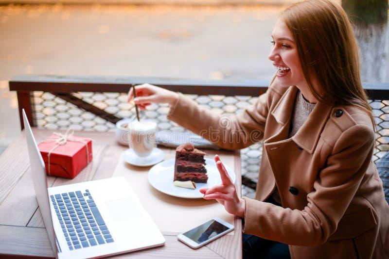 Une fille dans un café extérieur avec un ordinateur portable parlant à quelqu'un par l'intermédiaire d'un appel visuel, latte de  images stock