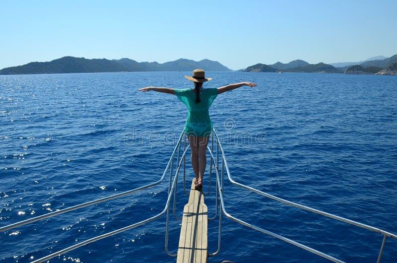 Une fille dans un chapeau de paille sur l'arc du yacht a tendu des bras image stock