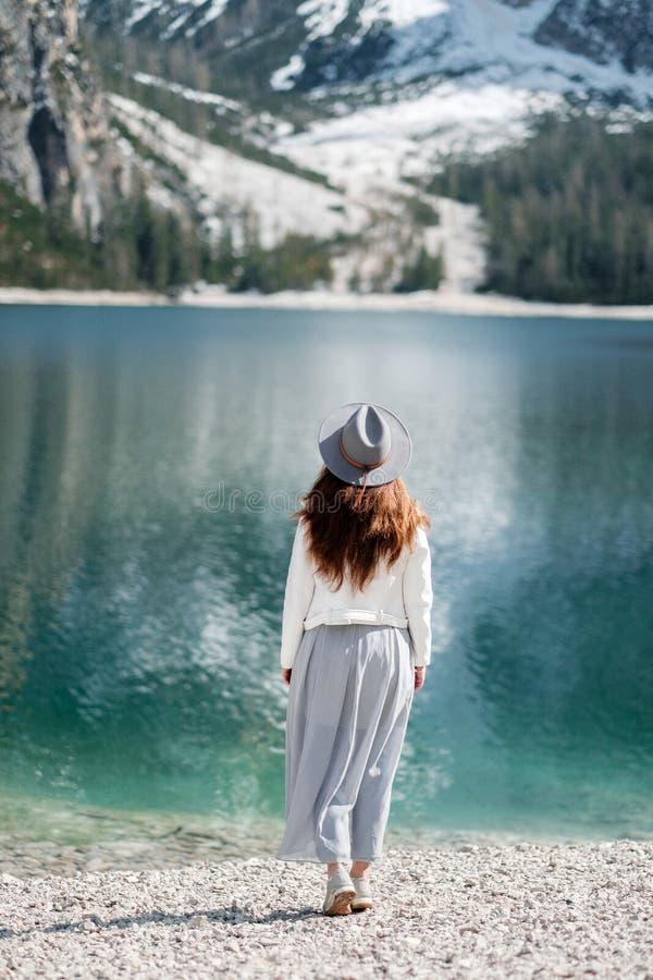 Une fille dans un chapeau et une longue robe marche le long du lac Lago di Bries dans le nord de l'Italie image libre de droits