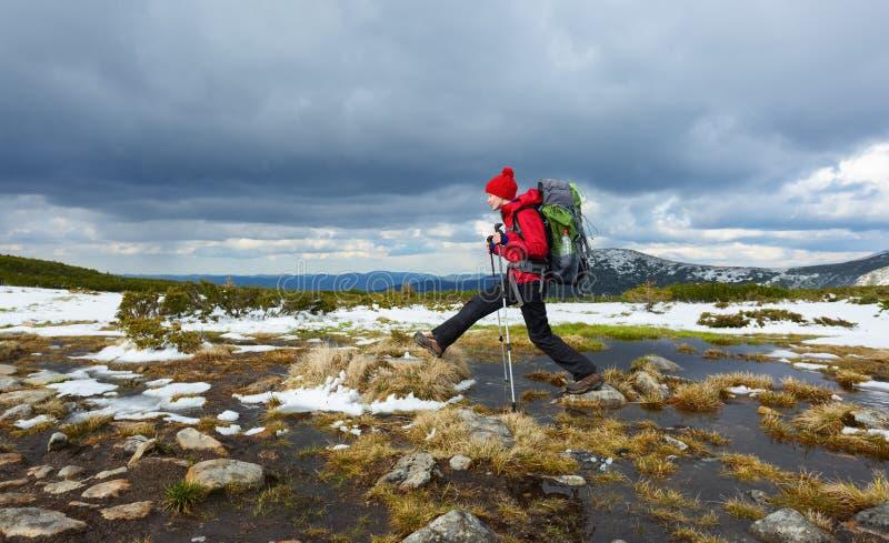 Une fille dans un chapeau rouge saute par-dessus des bosses parmi l'eau sur un neigeux images libres de droits