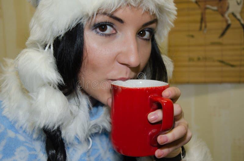 Une fille dans un costume d'hiver boit une boisson Tasse rouge fille caucasienne de bébé de brune jeune utilisant un chapeau lain image libre de droits