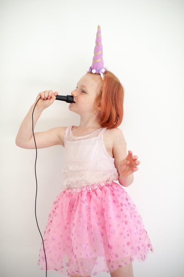 Une fille dans un costume de licorne chante dans un microphone images stock