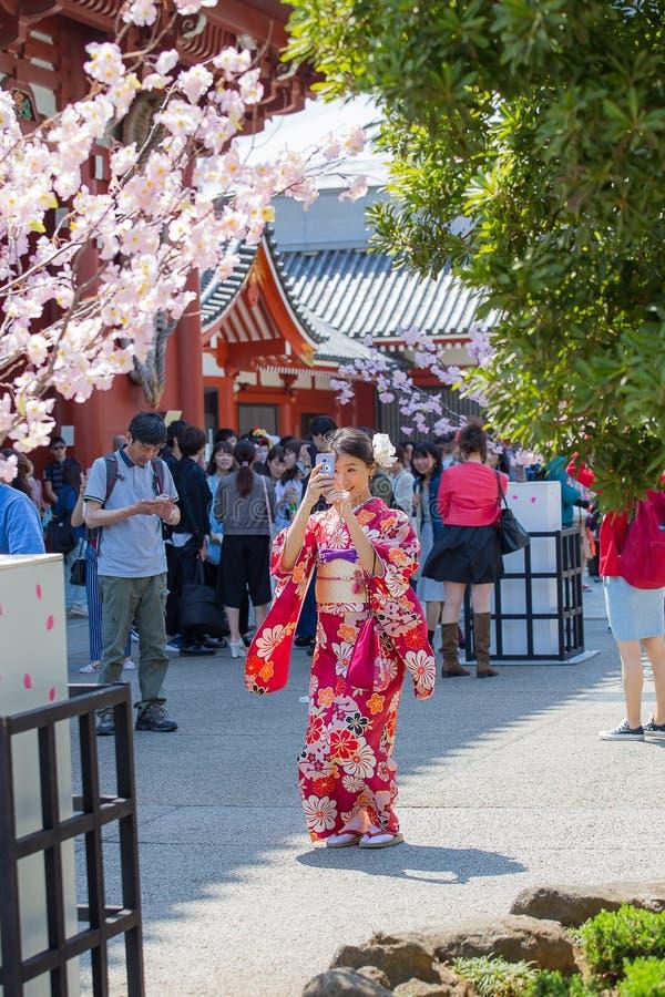 Une fille dans un costume de yukata prend une photo d'un smartphone au temple d'Asakusa à Tokyo, Japon photographie stock