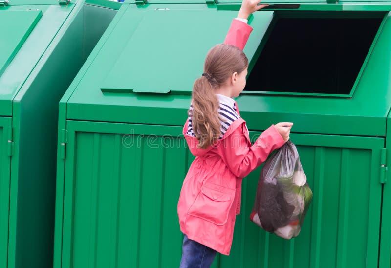 Une fille dans un imperméable rose a apporté un sac des déchets et le jette ouvrent le conteneur photos libres de droits