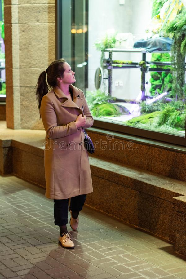 Une fille dans un manteau marche par les rues de nuit de la ville près des fenêtres de magasin photo stock